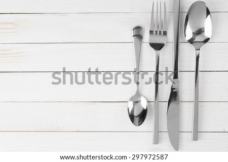 Cutlery set: knife, fork and spoons on white wooden background. - stock photo
