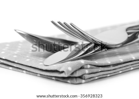 Cutlery set: spoon, fork and knife on napkin close-up. Monochrome black and white image. - stock photo