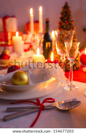 Cutlery with red ribbon on the holiday table - stock photo