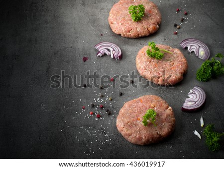 Cutlet. Raw beef and pork burgers and ingredients for cooking at slate background. - stock photo