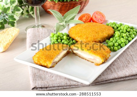 Cutlet stuffed with ham and melted cheese on complex background - stock photo