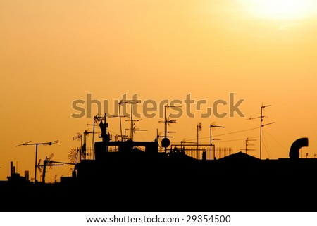 cutout of a sunset on a city roofs skyline - stock photo