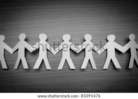Cutout  paper people on wooden table - stock photo