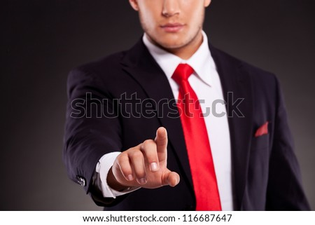 cutout picture of a young business man pushing a button with focus on his finger. against dark background - stock photo