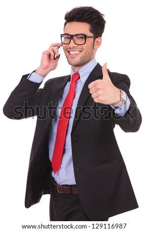 cutout picture of a young business man showing thumbs up sign and speaking at the phone while smiling to the camera on a white background - stock photo