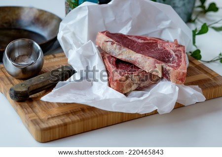 Cuts of raw beef on the cutting board with some green salad in the background - stock photo