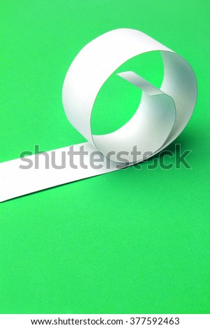 Cutted and rolled white paper with green  background - stock photo