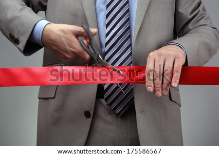 Cutting a red ribbon with scissors concept for new business venture or opening ceremony - stock photo