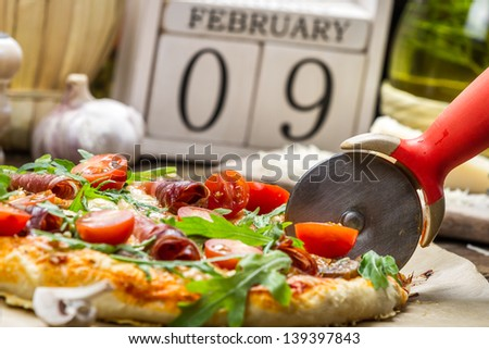 Cutting baked pizza in the background with calendar - stock photo