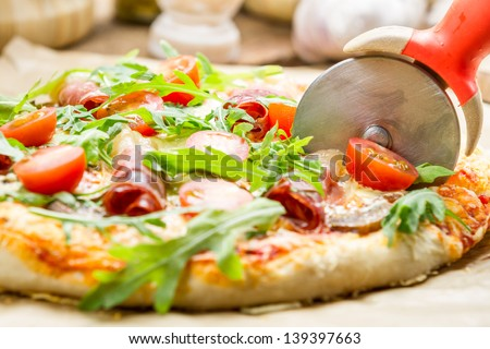 Cutting baked pizza with tomatoes and ham - stock photo