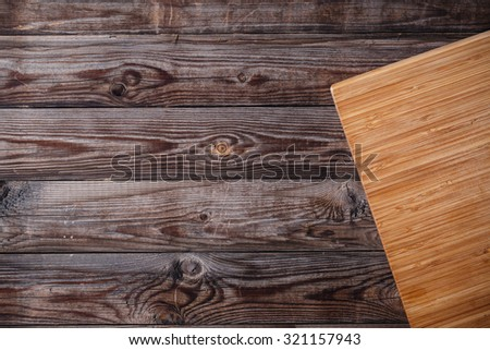 cutting board with space for text on old wooden background - stock photo