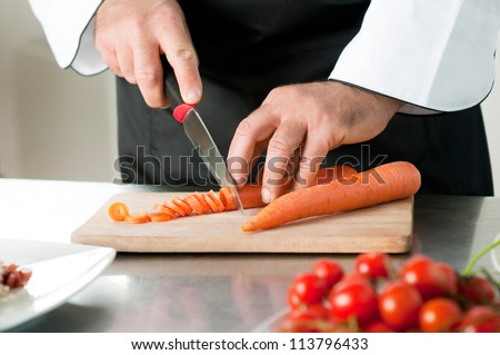 Cutting carrot on a wooden board for meal preparation at restaurant - stock photo