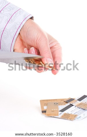 Cutting credit cards by scissors over white background - stock photo