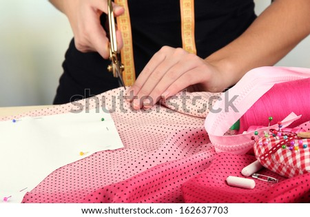 Cutting fabric with tailors scissors  - stock photo