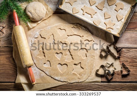 Cutting gingerbread cookies for Christmas - stock photo