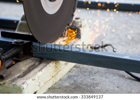 Cutting metal with grinder. Sparks while grinding iron. - stock photo