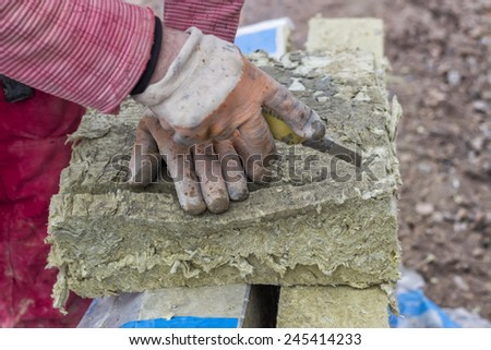 Cutting mineral wool panel with a craft knive at construction site. Selective focus.  - stock photo