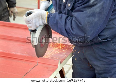 Cutting of heat insulated galvanized corrugated sandwich roof panel, workers hands angle grinder tool - stock photo