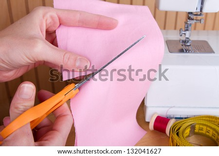 Cutting out a piece of pink fabric with scissors, sewing machine in background - stock photo