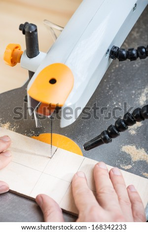 Cutting plywood board by using electrical jigsaw. - stock photo