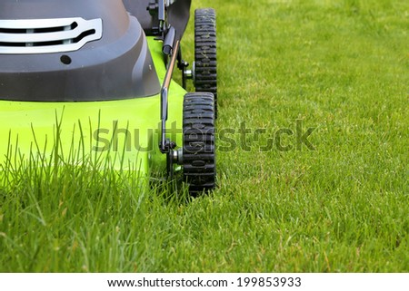 cutting the grass with electric lawn mower - stock photo