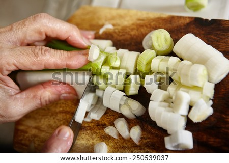 Cutting the leek on wooden cutting board, slight movement blur might be noticeable - stock photo