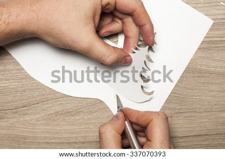 Cutting the New Year tree out of paper. - stock photo