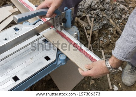 cutting tile with cutting tool at the building site - stock photo