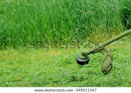 Cutting torch of a manual lawn-mower against a mowed grass. - stock photo