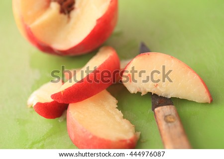 Cutting up a fresh, juicy peach into slices with a paring knife - stock photo