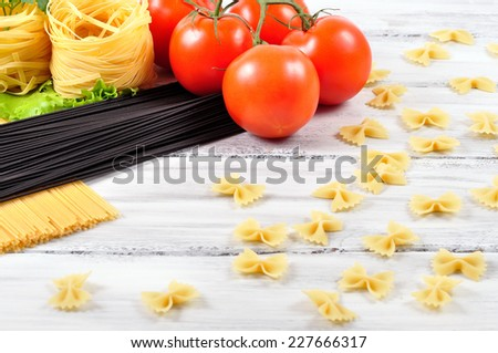 cuttlefish ink pasta and egg pasta with tomatoes on a white wooden background - stock photo