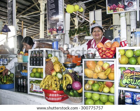 CUZCO, PERU - JAN 18, 2015: friendly local woman sells fresh juices to tourists at the central market in Cuzco, Peru. Beside local fruit she also offers soft drinks. - stock photo