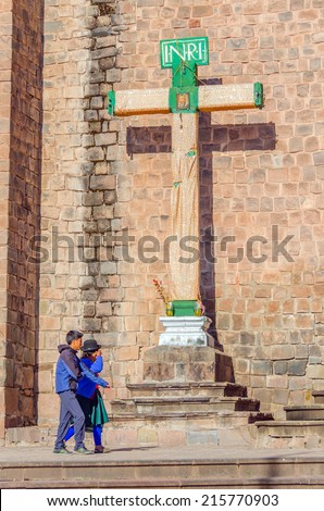 CUZCO, PERU, MAY 1, 2014:  Local couple pass by the cross in front of San Francisco church - stock photo