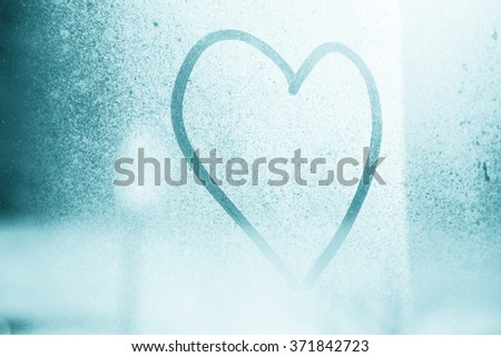 Cyan blue color shine abstract blurred love heart symbol drawn by hand on the frozen glass window with soft bright blue color background. Selective focus and serenity pastel pantone color tone used. - stock photo