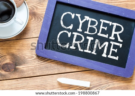 Cyber crime handwritten with white chalk on a blackboard, cup of coffee and biscuit on a wooden background - stock photo