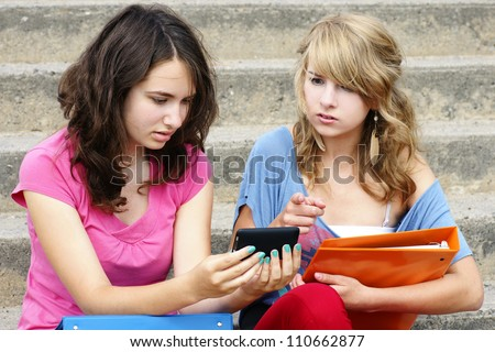 Cyber or online bullying concept with two young women students or teenager girls shocked at the text they are reading on their cell phone, perfect for awareness. - stock photo