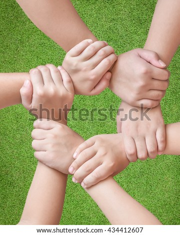 Cycle of children young generation's hands holding together on green grass lawn environment background: Circle ring of people friendship connectivity togetherness unity Global linkage CSR ESG concept  - stock photo