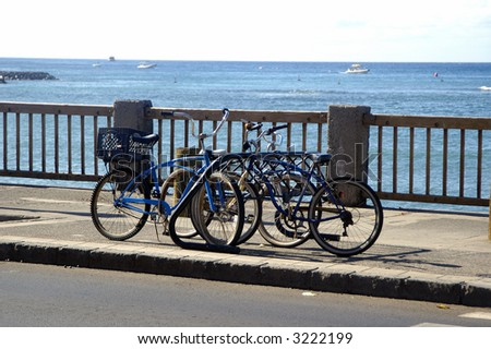 Cycles locked in a stand against a ocean background - stock photo