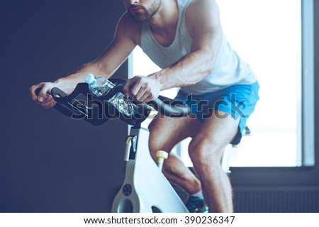 Cycling and energy. Part of young man in sportswear cycling at gym - stock photo