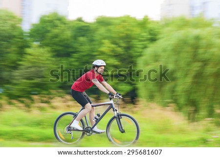 Cycling and Sport Concepts: Handsome Caucasian Rider Having a Bike Trip Outdoors in Forest. Horizontal Shot - stock photo