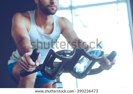 Cycling at gym. Part of low angle view of young man in sportswear cycling at gym - stock photo