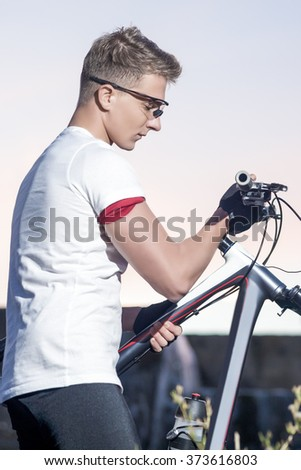 Cycling Concept and Ideas. Handsome Sportive Caucasian Cyclist With MTB Bike Outdoors. Vertical Image Orientation - stock photo
