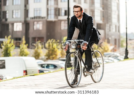 Cycling is the way to progress! Full length of handsome young businessman looking forward while riding on his bicycle  - stock photo