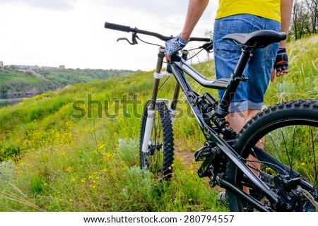 Cyclist and his Bike on the Beautiful Spring Mountain Trail - stock photo