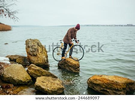 Cyclist climbing on a rock - stock photo