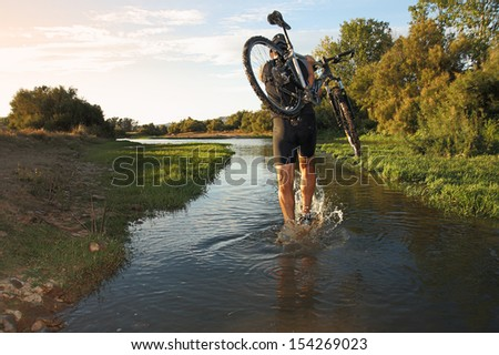 cyclist crossing river - stock photo