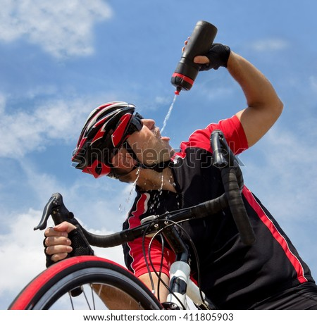 Cyclist drinking from a bottle while riding a bike on blue background.Thirsty bicyclist drinks drink from the bottle.Refreshing the tired cyclists.Biker on bike drinks water from bottle over his head. - stock photo