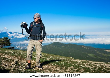 cyclist holds a helmet, mountains in background - stock photo