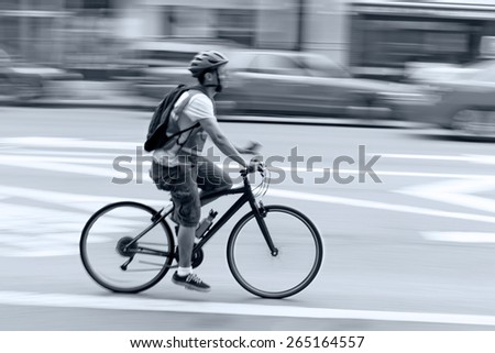 cyclist in traffic on the city roadway  motion blur and blue tonality  - stock photo