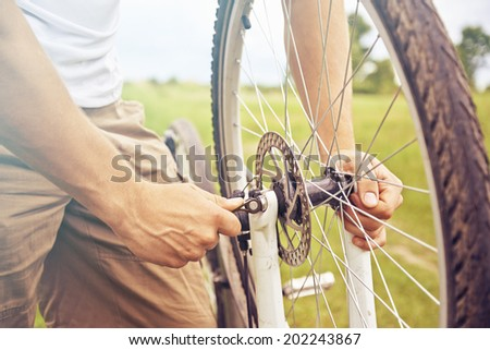 Cyclist man checks wheel of bicycle in summer park, face is not visible, repair of bicycle - stock photo
